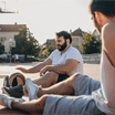 Group of men, friends playing street basketball on a sunny day outdoors, taking a break.