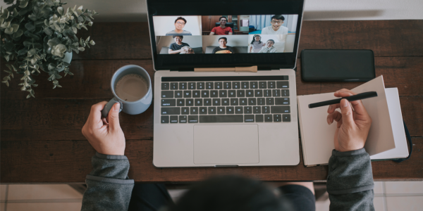 A man working at home using laptop video conference call meeting with headset